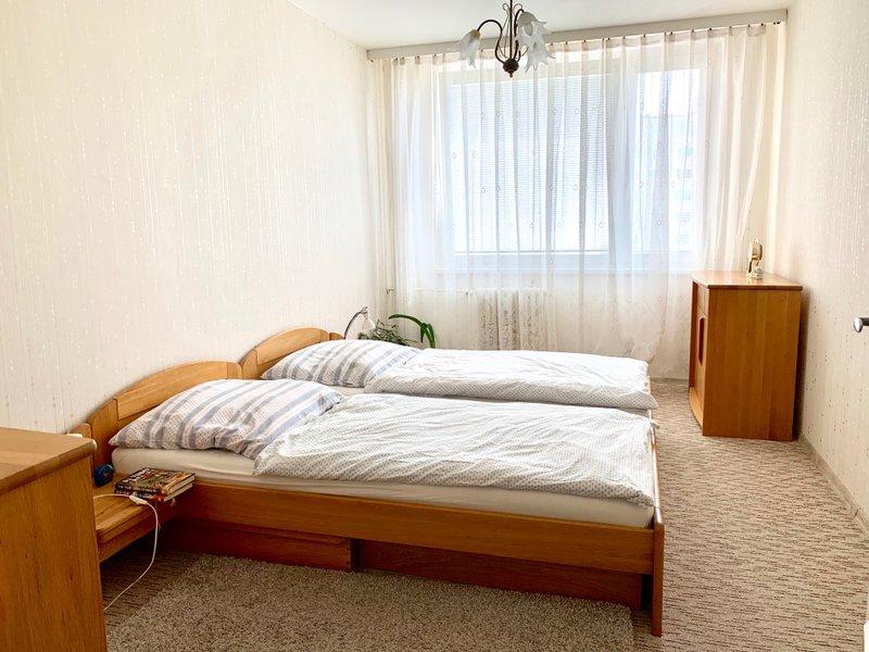 ložnice s dvoupostelí, plastové okno, skříň a koberec