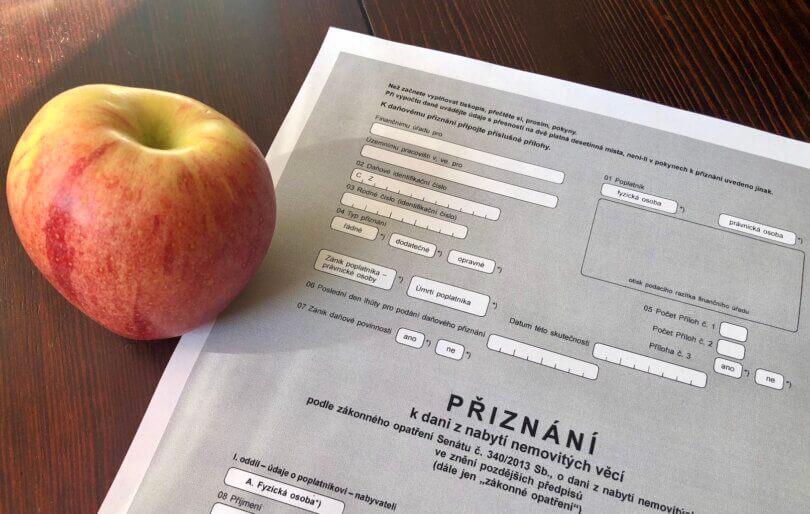 """jablíčko na stole, vedle něho leží formulář """"daňové přiznání k dani z nabytí nemovitých věcí"""""""