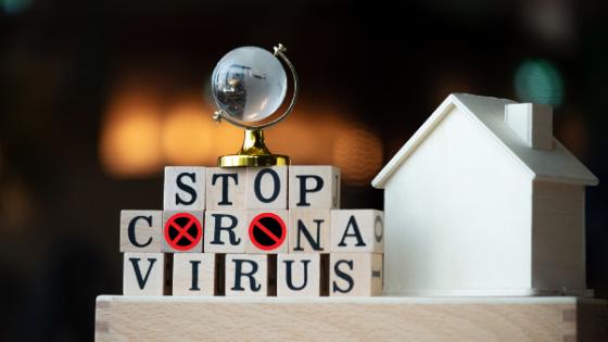 """nápis """"stop coronavirus"""" postavený z kostek a vedle něj dřevěný domeček"""