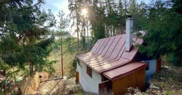 chata v lese, střecha, pohled na údolí a zapadající slunce