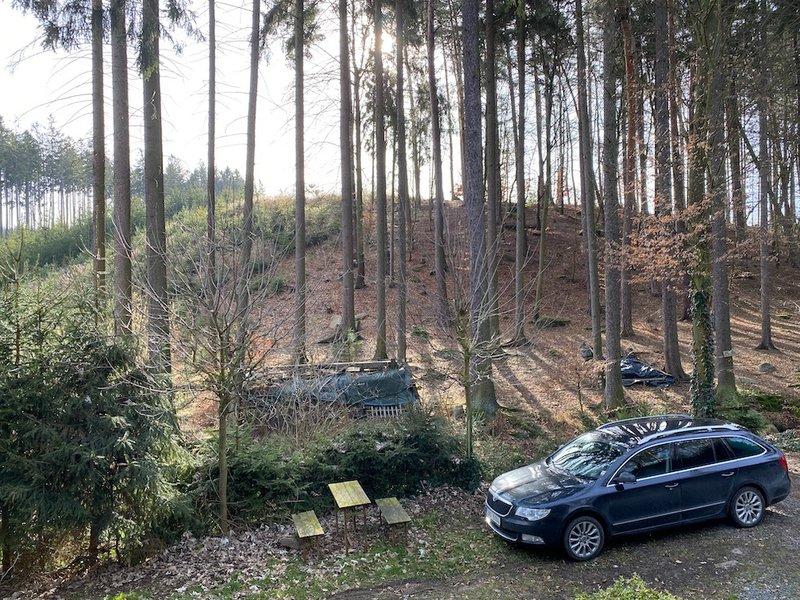 zaparkované auto, jehličnatý les, lavička a stolek v lese