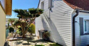 obložená rodinný dům se sedlovou střechou, trávník a malý strom