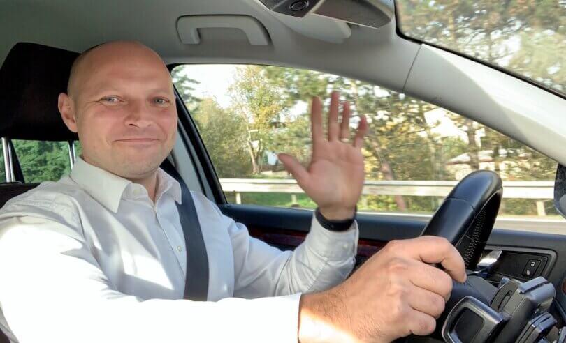 mladý muž jede v autě, řídí, usmívá se do objektivu a mává