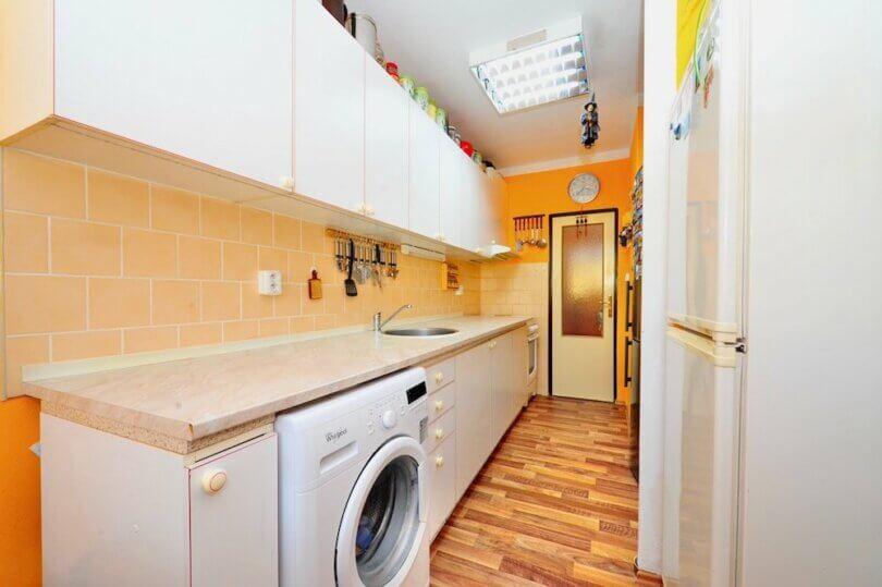 Bílá kuchyňská linka, lednice, dřez a dveře