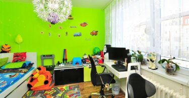 místnost se zelenou stěnou, židle, hračky, topení a lustr ve tvaru květiny