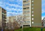 břízy, panelové domy a modré nebe s obláčky