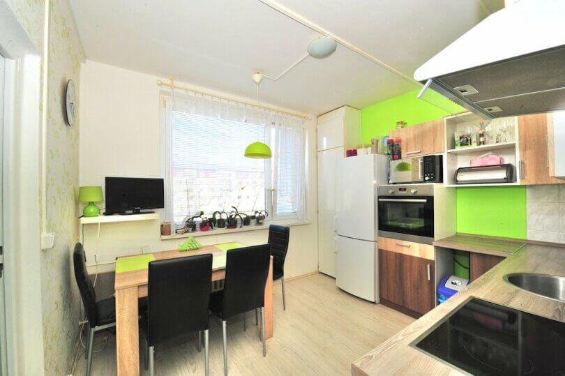 kuchyňská linka, jídelní stůl, trouba, zelená stěna