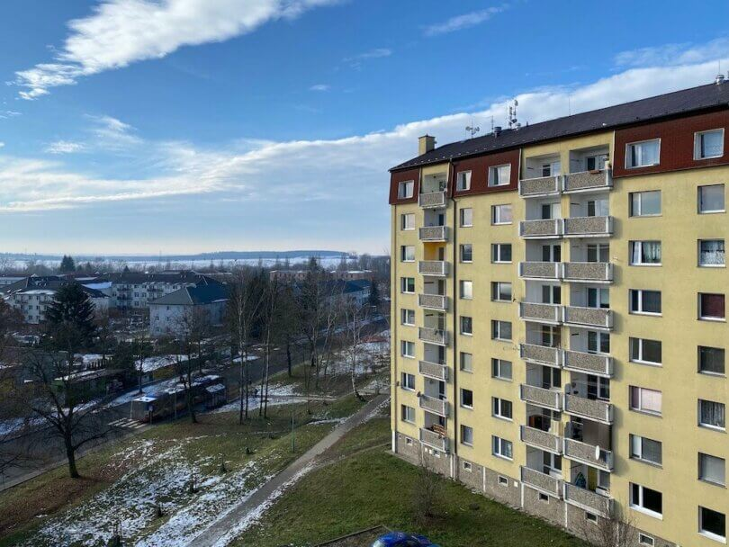 zateplený panelový dům s lodžiemi, silnice, chodník, zbytky sněhu a modrá obloha