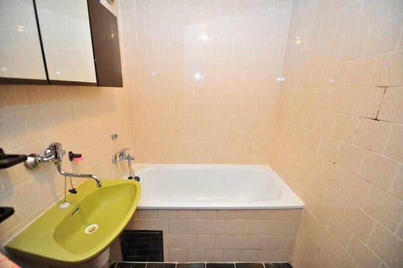 koupelna se zeleným umyvadlem, zrcadlo, malá vana a obklady