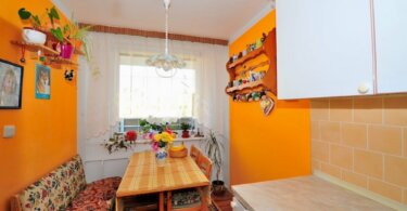 jídelní kout se stolem, lavicí, židlemi a část kuchyňské linky