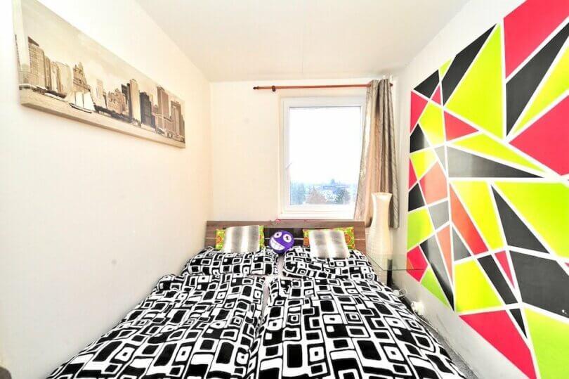 místnost s postelí, plastové okno a barevná stěna