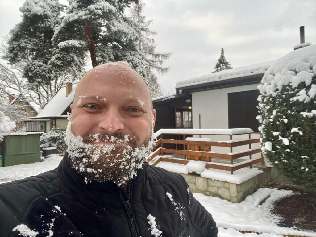 plešatý muž s vousy od sněhu, usmívá se před zasněženou chatou
